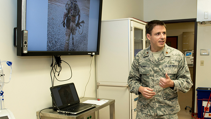 An airman standing in an office with a television on behind him.