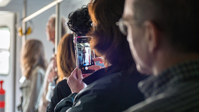 An image of a group of adults standing in line with emphasis on one of the adults cellular phone.