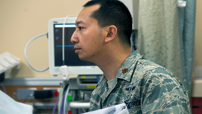 An image of an airman in a patient room looking to the left.