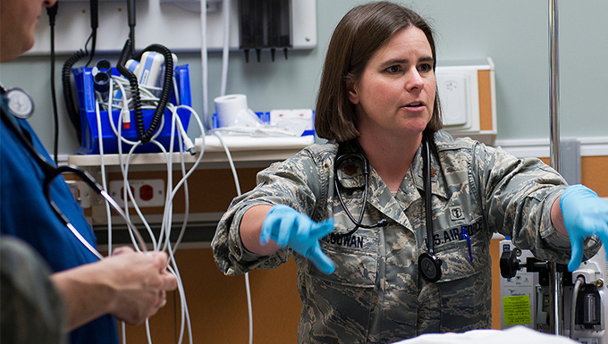 An airmen with latex medical gloves on in a patient room.