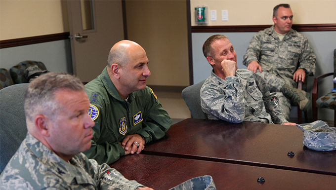 A group of airman sitting around a table inside.