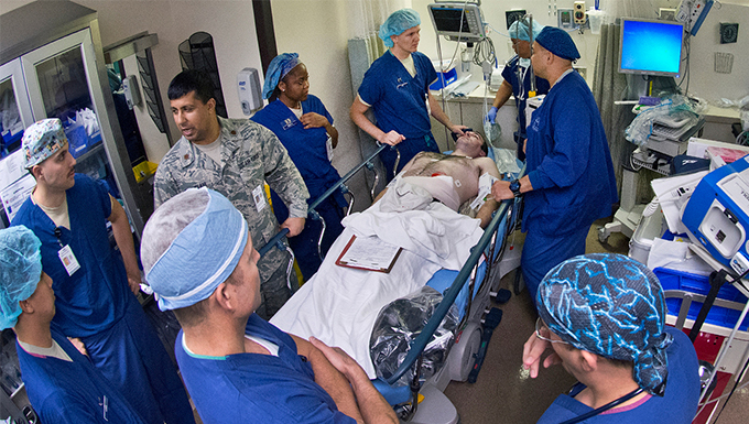 A group of doctors and nurses standing around a patient in the operating room.