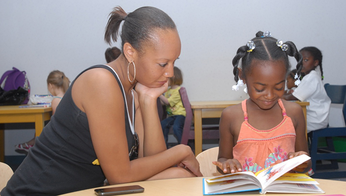 A woman and a child reading a book together.