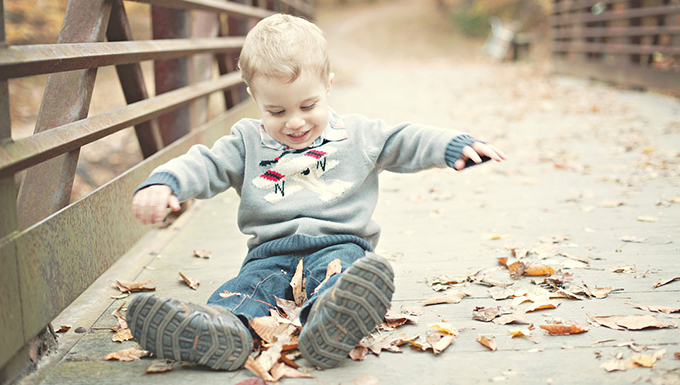 A child sitting on a pedestrian bridge playing.
