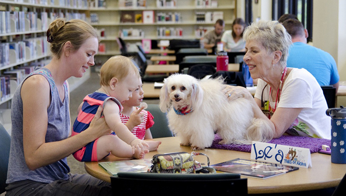 A group of people sitting down at the library with a dog.