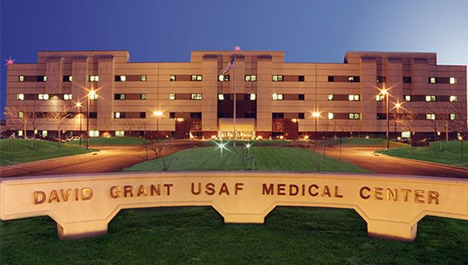 An image of David Grant USAF Medical Center's sign and the facility.