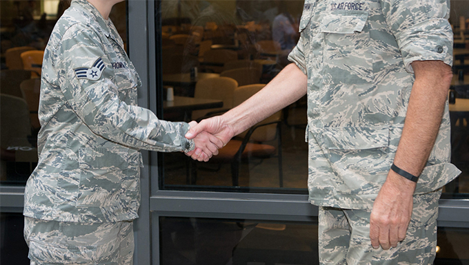 An image of two airman shaking hands in front of a window.