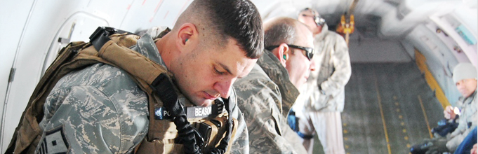 An airmen sitting with his head down and eyes closed.