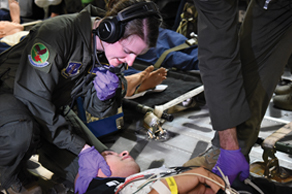 An airman helping a patient on a military aircraft.