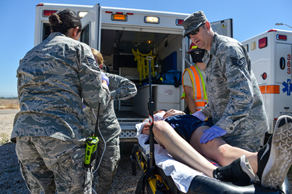 A group of airmen loading a patient into an ambulance.