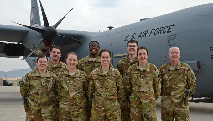 A group of airmen standing in front of a military aircraft outdoors.