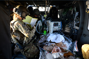 A group of airmen transporting an injured patient in a military aircraft.