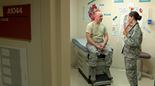 An Airman talking to a male patient at the doctors office.