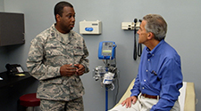 An Airman talking to an older male patient at the doctors office.