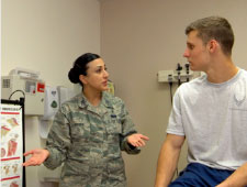 Image of an Airman talking to a patient