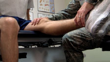 Image of an Airman treating a patient's leg