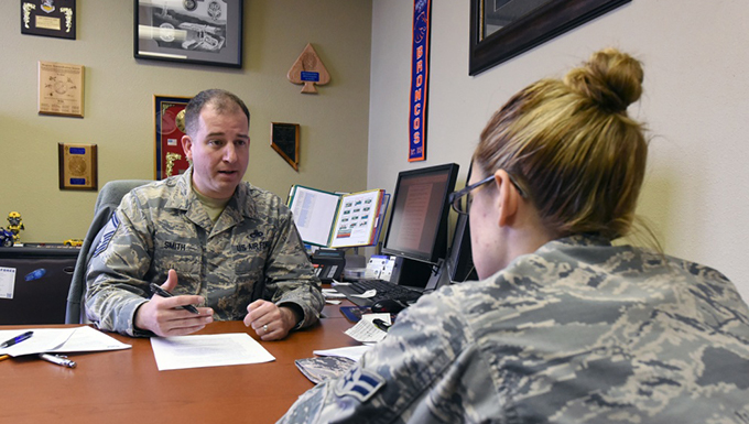 Two airmen speaking in an office at a table.